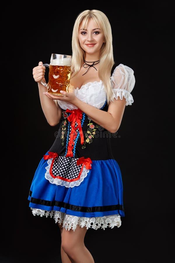 Den unga sexiga kvinnan som bär en dirndl med öl, rånar på svart bakgrund arkivfoton