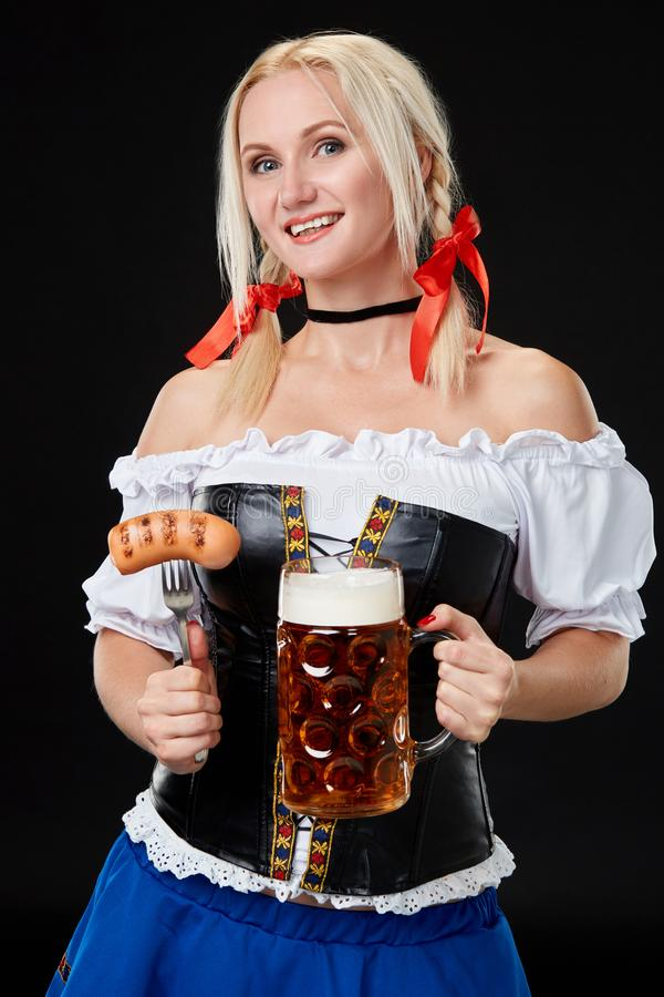 Den unga sexiga kvinnan som bär en dirndl med öl, rånar på svart bakgrund arkivbilder