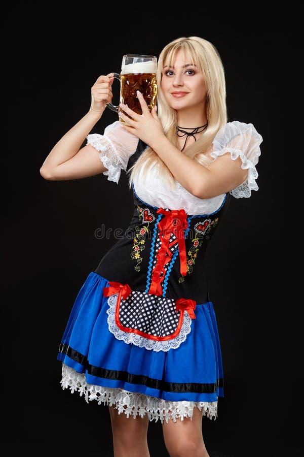 Den unga sexiga kvinnan som bär en dirndl med öl, rånar på svart bakgrund royaltyfri foto