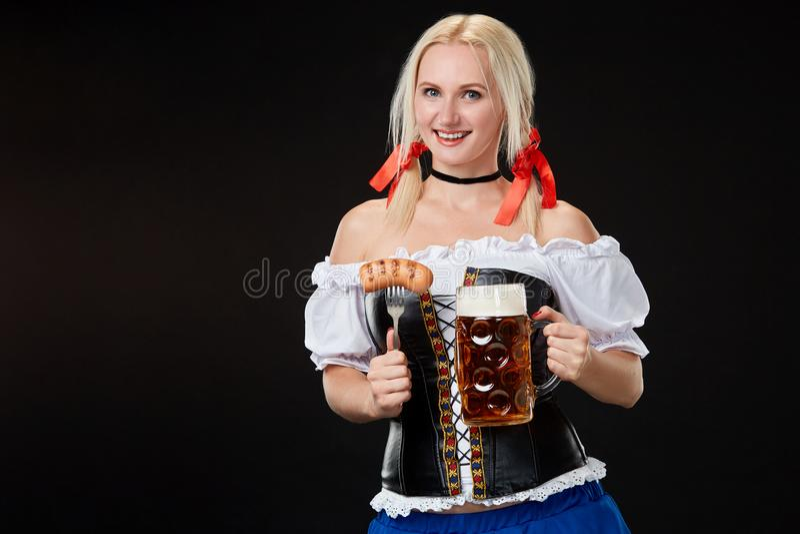 Den unga sexiga kvinnan som bär en dirndl med öl, rånar på svart bakgrund royaltyfri bild