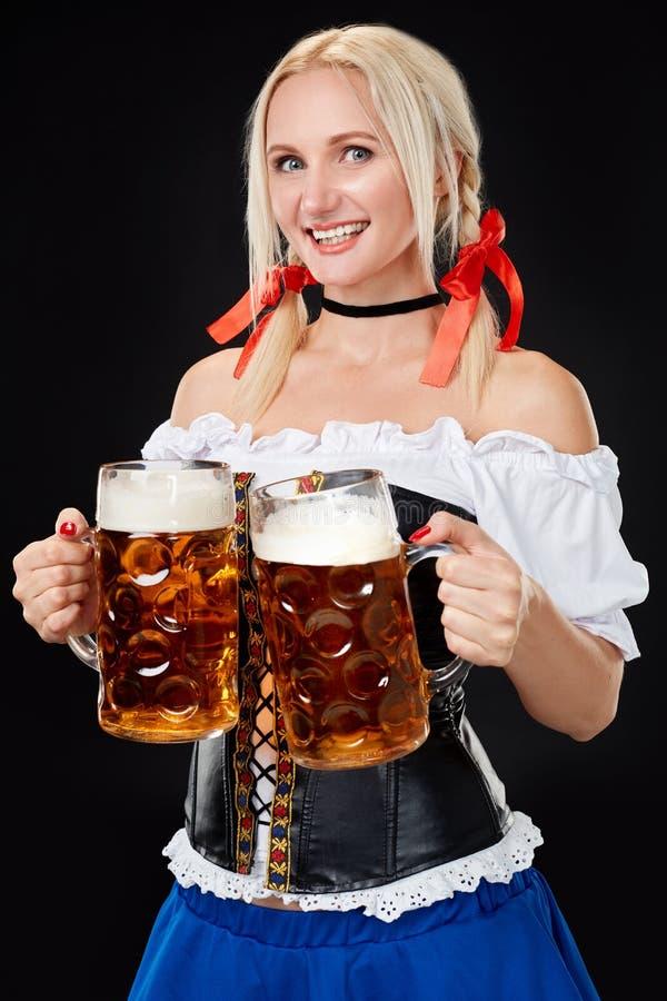 Den unga sexiga kvinnan som bär en dirndl med öl två, rånar på svart bakgrund arkivbilder