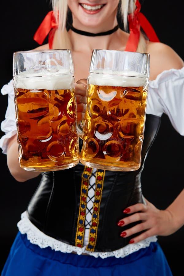 Den unga sexiga kvinnan som bär en dirndl med öl två, rånar på svart bakgrund royaltyfria foton