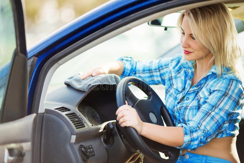 Den unga sexiga kvinnan tvättar bilen royaltyfri bild