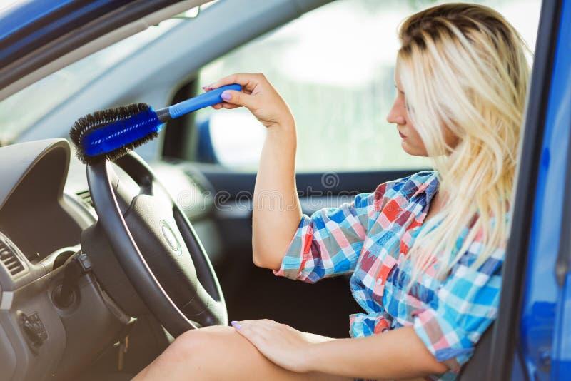 Den unga sexiga kvinnan tvättar bilen arkivfoto