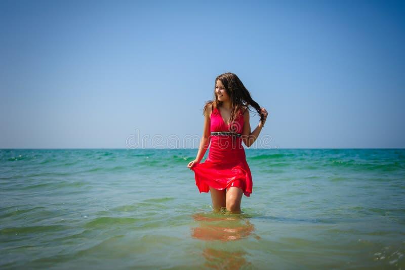 Den unga sexiga långhåriga brunetten i röd strandklänning står i turkosvattnet av havet på en varm dag h?rligt le arkivbilder