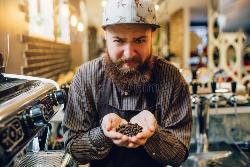 Den unga skäggiga baristaen känner sig äckla Han rymmer kaffebönor i händer och blick på kamera Grabben är uppriven Han bär förkl royaltyfri foto