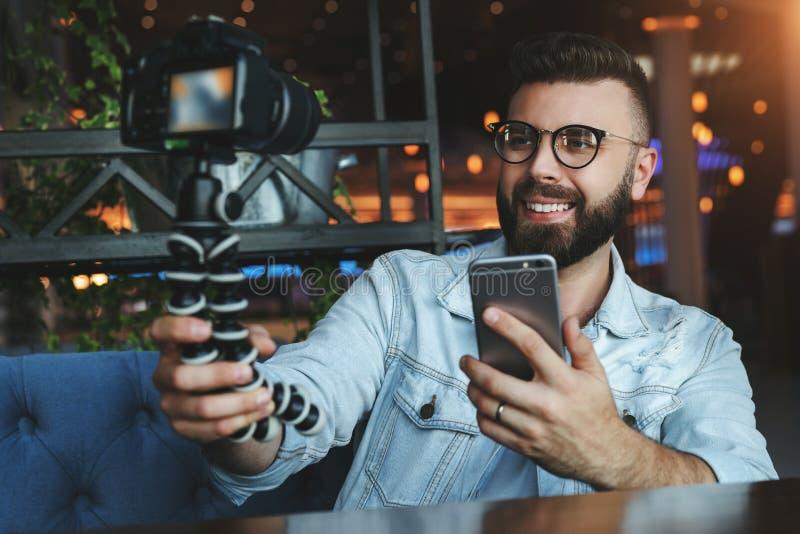 Den unga skäggiga manliga videopd bloggeren skapar det videopd innehållet för hans kanal Den lyckliga grabben skjuter videoen som royaltyfri bild