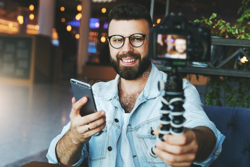 Den unga skäggiga manliga videopd bloggeren skapar det videopd innehållet för hans kanal Den lyckliga grabben skjuter videoen som royaltyfri fotografi
