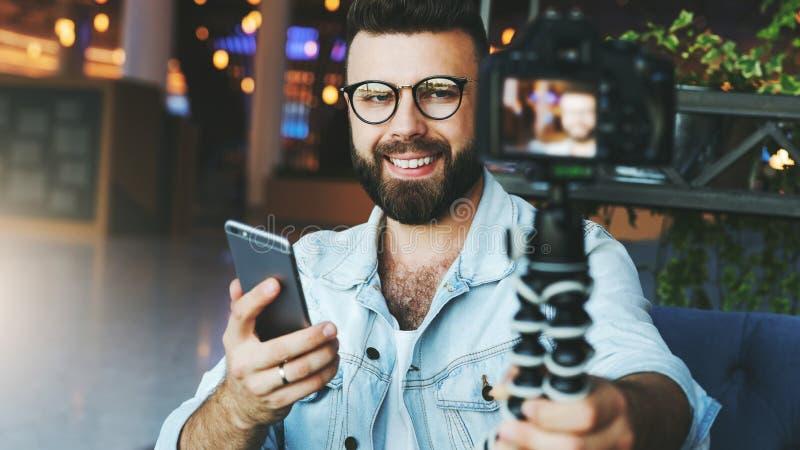 Den unga skäggiga manliga videopd bloggeren skapar det videopd innehållet för hans kanal Den lyckliga grabben skjuter videoen som arkivfoton