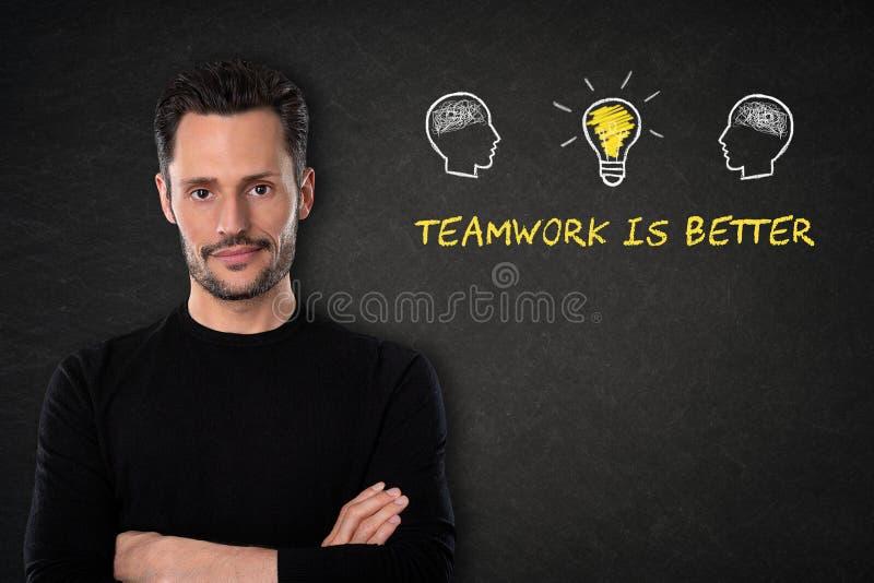 Den unga skäggiga mannen med korsade armar, huvud med hjärnor, lightbulb-idén och text 'teamwork är bättre 'på en svart tavlabakg royaltyfria bilder