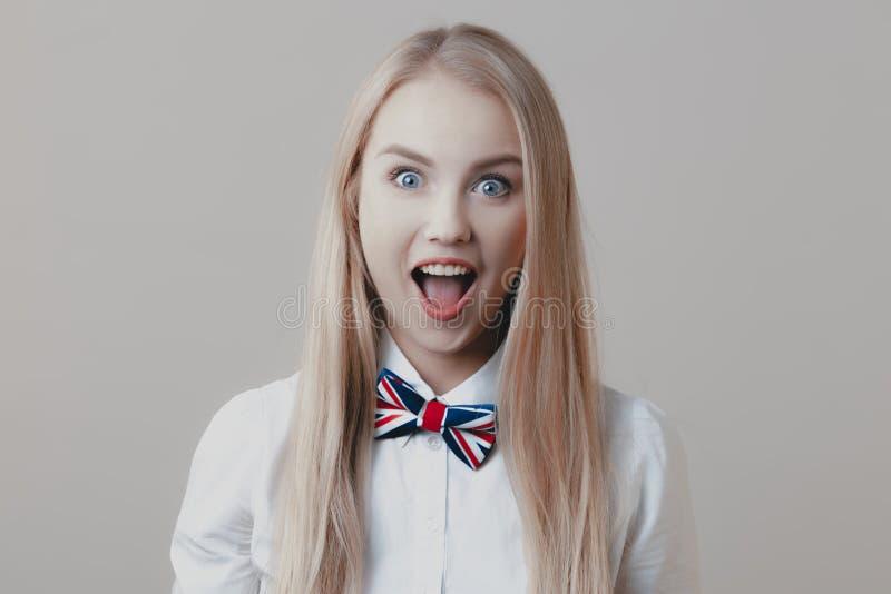 Den unga skämtsamma gulliga blondinen med flugan öppnar hennes mun i surpri arkivbilder