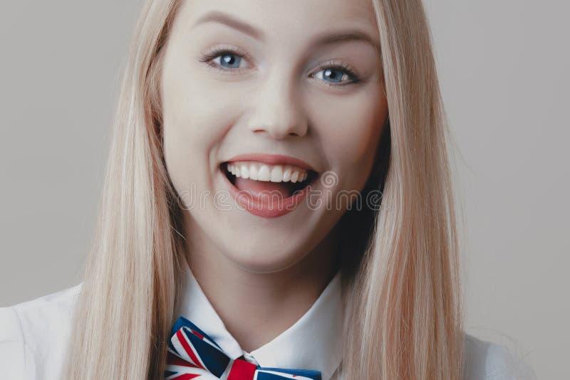 Den unga skämtsamma gulliga blondinen med flugan skrattar royaltyfri bild