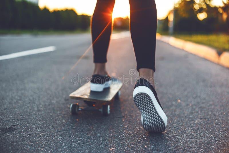 Den unga skateboarderen lägger benen på ryggen ridning på skateboarden royaltyfri fotografi