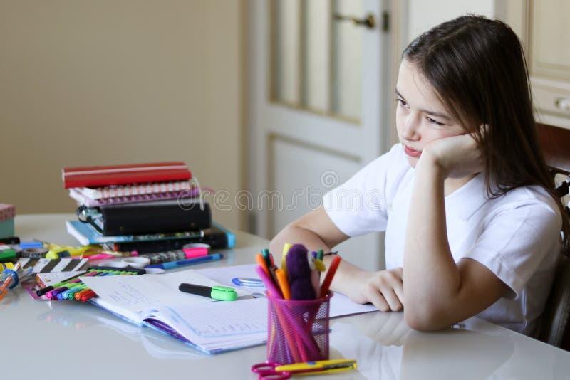 Den unga skolflickan är uppriven och trött av att göra skolaläxa arkivfoto