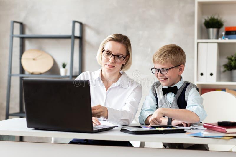 Den unga skolpojken i tröja och hans charmiga lärare i den vita blusen sitter bak skrivbordet och att arbeta med bärbara datorn arkivbild