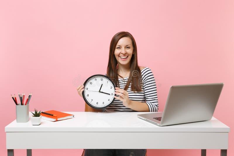 Den unga skratta kvinnan i tillfällig kläder som rymmer den runda ringklockan, sitter arbete på det vita skrivbordet med den mode arkivfoton