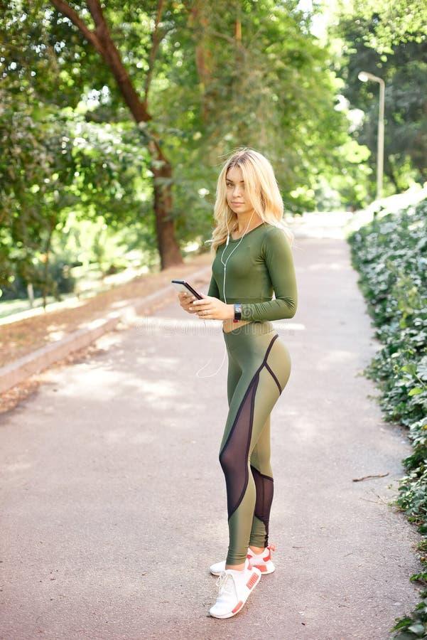 Den unga slanka kvinnan med en sportig kropp, ett lång blont hår som är iklädda en sportöverkant och damasker, förbereder sig för fotografering för bildbyråer