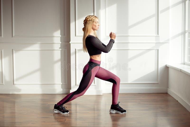 Den unga slanka kvinnan med ett långt blont hår för idrotts- kropp och att bära en svart sportöverkant och damasker, utför en övn arkivfoto