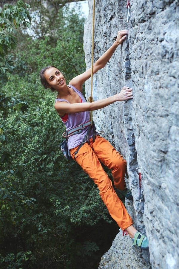 Den unga slanka kvinnan vaggar klättraren som klättrar på klippan arkivfoto