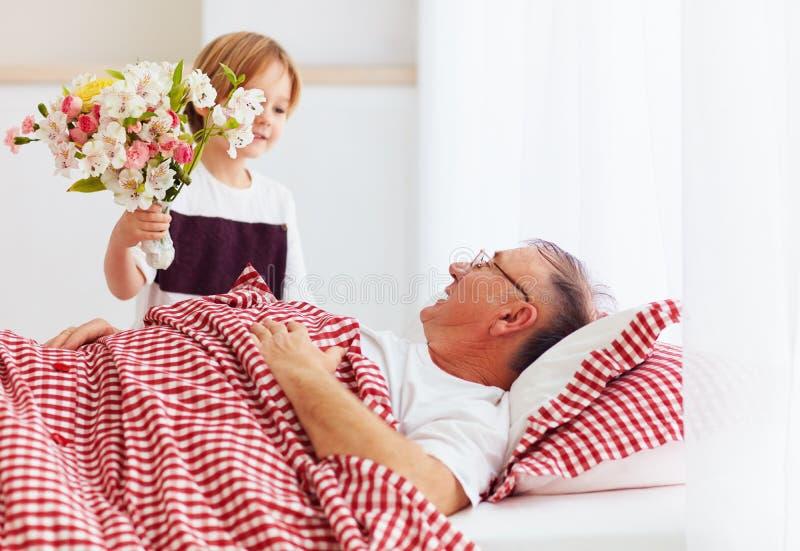 Den unga sonsonen med blommabuketten kom att besöka hans sjuka morfar i sjukhussal arkivbilder