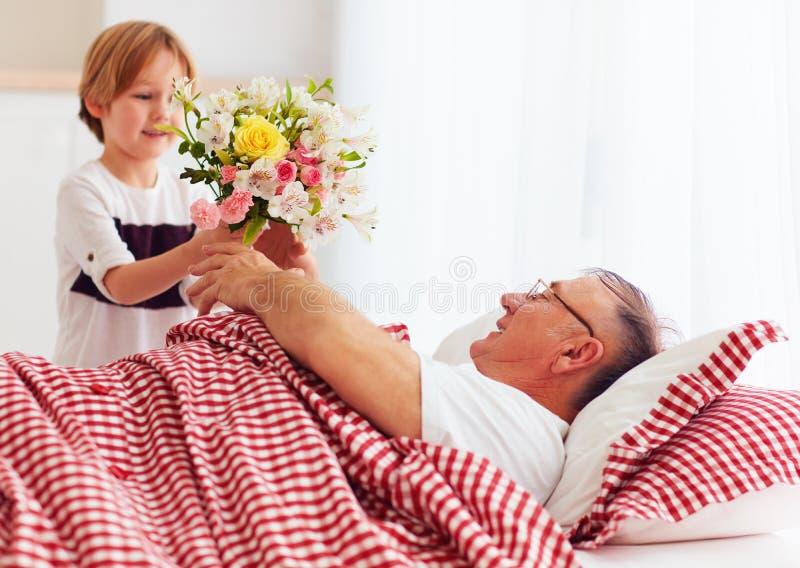 Den unga sonsonen med blommabuketten kom att besöka hans sjuka morfar i sjukhussal royaltyfri foto
