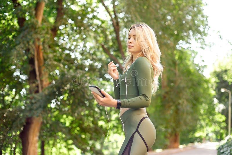 Den unga spensliga kvinnan med en sportkropp, ett lång blont hår som är iklädda en sportöverkant och damasker, förbereder sig för arkivfoton