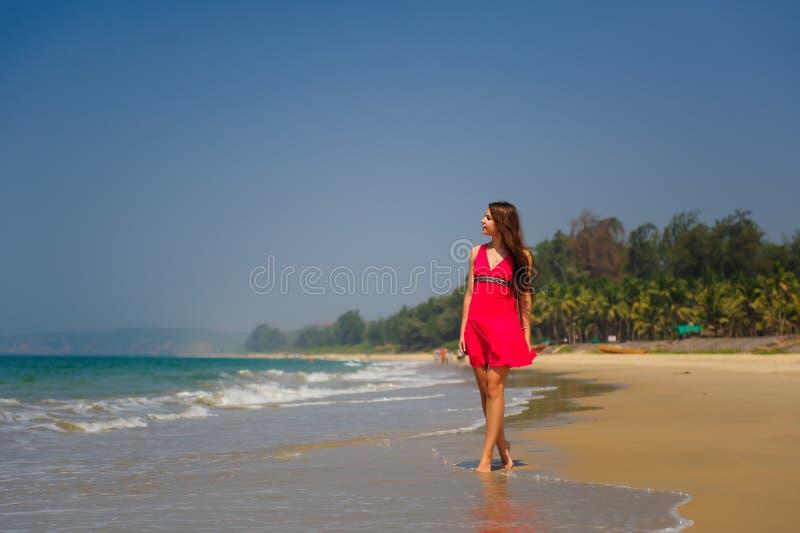 Den unga spensliga långhåriga brunetten i röd klänning går barfota på den tropiska stranden längs bränningen mot havet och den bl arkivfoton