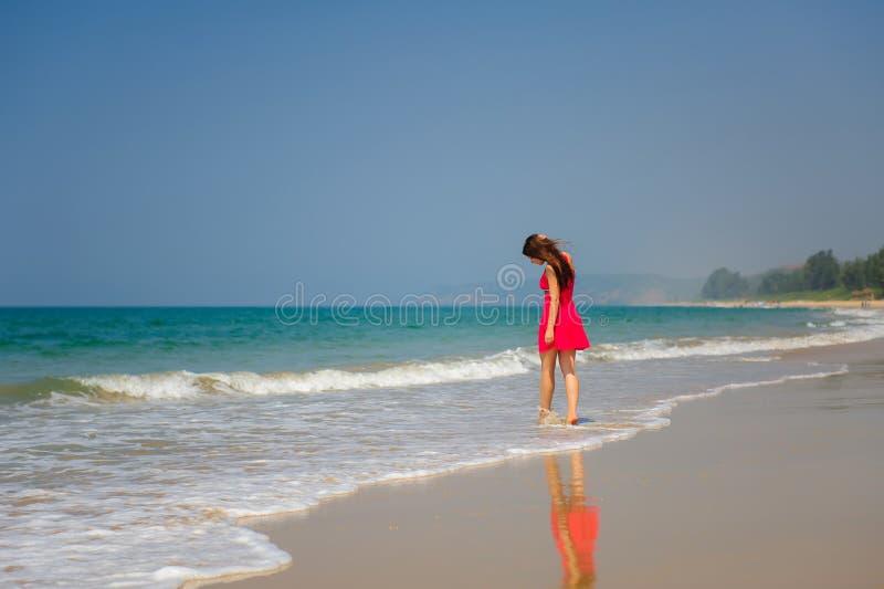 Den unga spensliga långhåriga brunetten i röd klänning går barfota på den tropiska stranden längs bränningen mot havet och den bl arkivbild