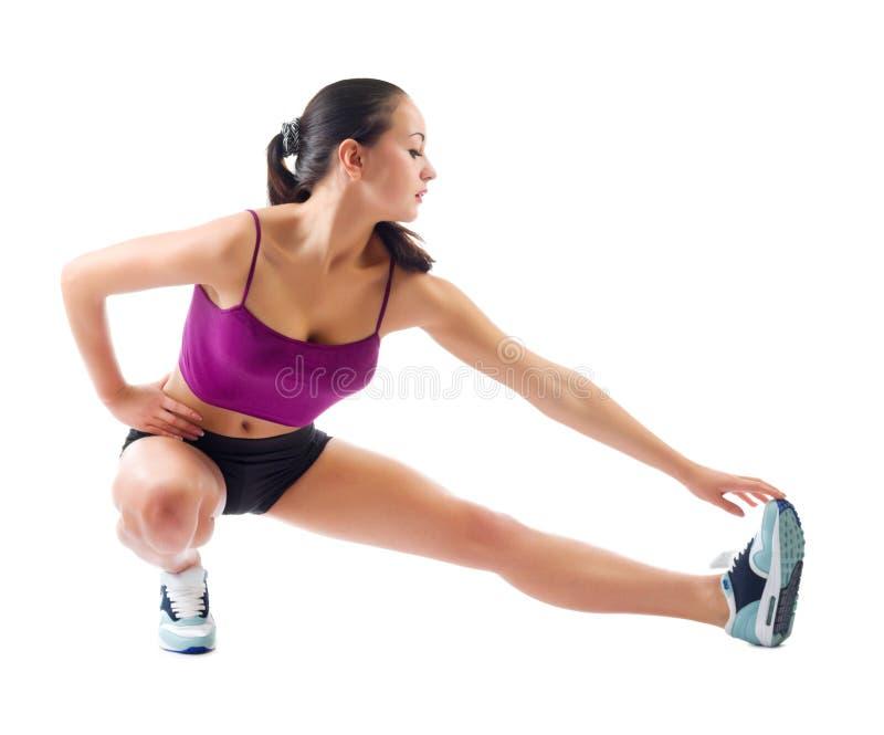 Den unga sportiga flickan gör gymnastiska övningar royaltyfri bild