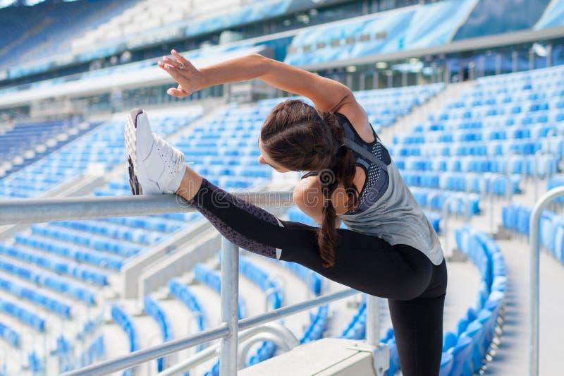 Den unga sportiga flickan med en brunbränd hud gör ett baner i stadion Kvinnan drar upp benet och att göra uppvärmningen royaltyfri fotografi