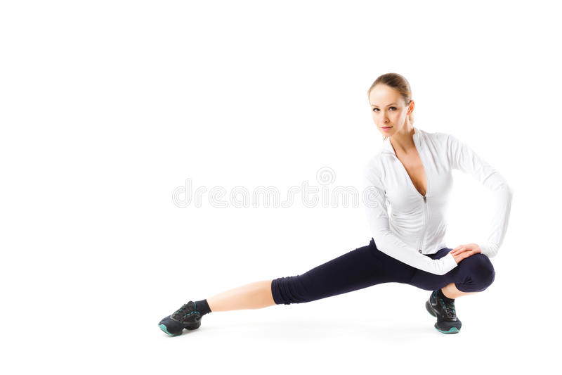 Den unga sportiga flickan som gör sträckning, övar sammanträde på golvet royaltyfria bilder