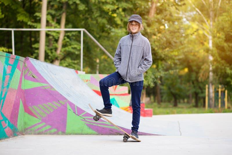 Den unga sportiga flickaridningen p? longboard parkerar in arkivfoto