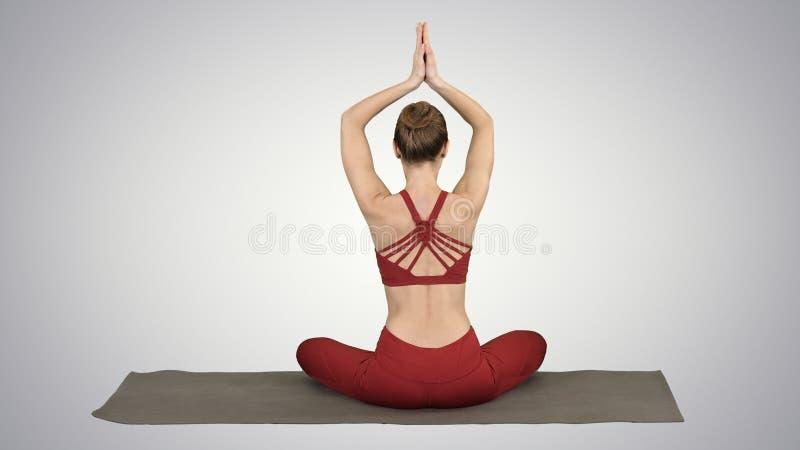 Den unga sportiga kvinnan som sitter i lotusblomma, poserar, sammanfogar händer ovanför hennes huvud på lutningbakgrund royaltyfri foto