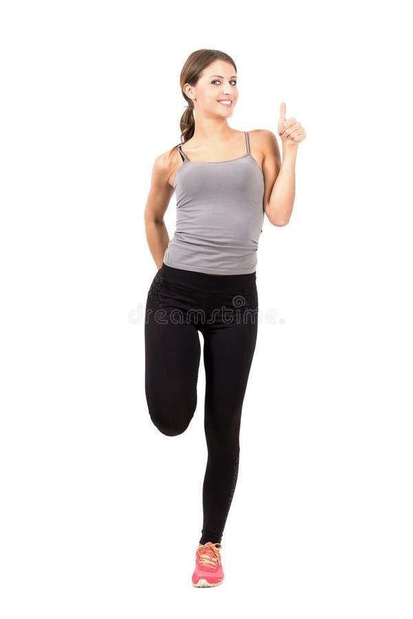 Den unga sportiga kvinnan som sträcker benet med tummar gör en gest upp royaltyfri fotografi