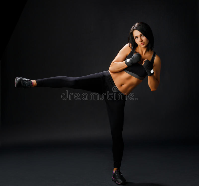 Den unga sportive kvinnan gör taebo-sidan att lägga benen på ryggen spark arkivbild