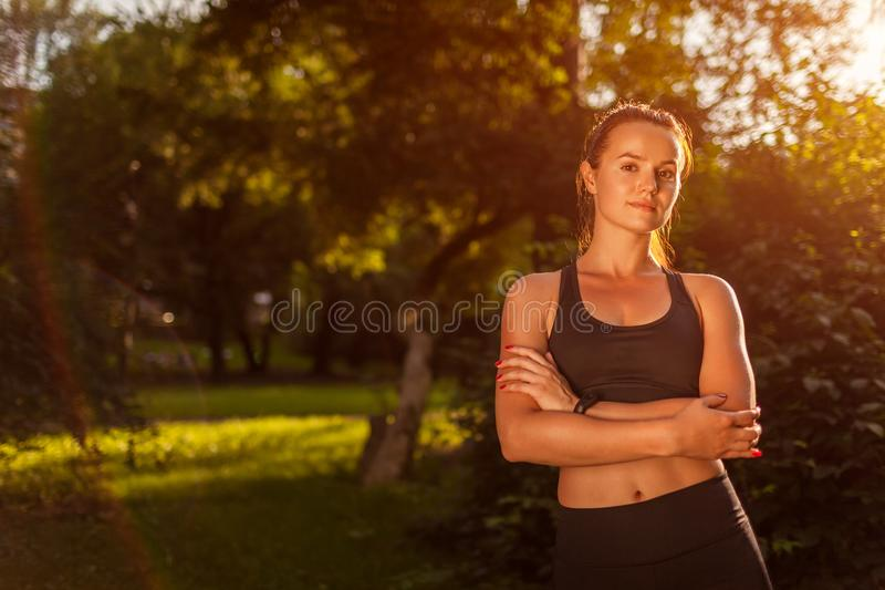 Den unga sportive kvinnan som ser kameran med händer, korsade i sommar parkerar Starkt lyckligt le för flicka Sund livsstil royaltyfri bild