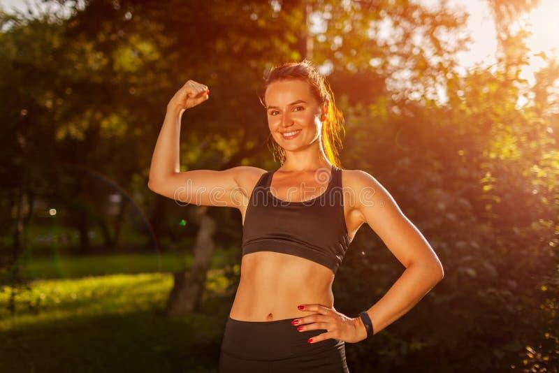 Den unga sportive kvinnavisningbicepens tränga sig in i sommar parkerar Starkt lyckligt le för flicka Sund livsstil royaltyfri fotografi