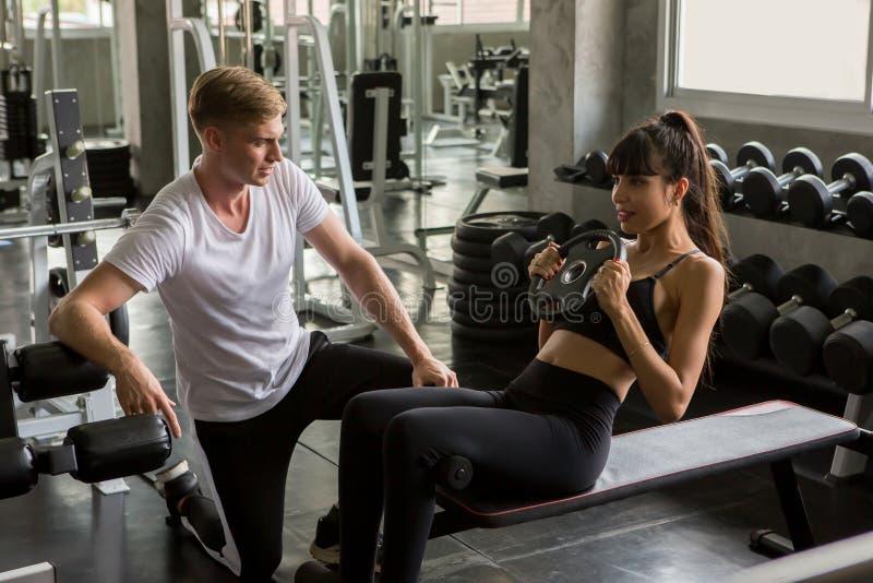 den unga sportkvinnan att göra som för övning sitter, ups på bänken med den personliga instruktören i konditionidrottshall Muskul arkivfoto