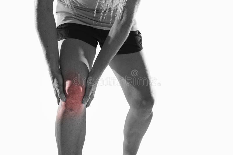 Den unga sportkvinnan med starka idrotts- ben som rymmer knäet med händer smärtar in, lidandeligamentskada royaltyfri foto