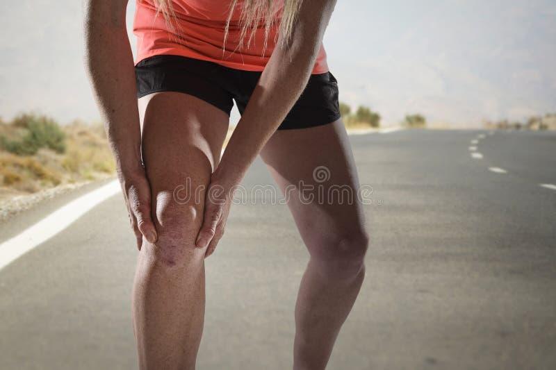 Den unga sportkvinnan med starka idrotts- ben som rymmer knäet med händer smärtar in, lidandeligamentskada arkivfoton
