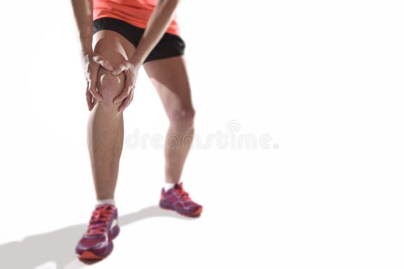 Den unga sportkvinnan med starka idrotts- ben som rymmer knäet med händer smärtar in, lidandeligamentskada arkivbilder