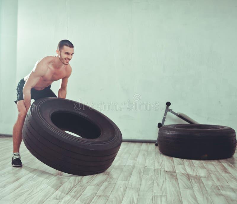 Den unga sportmannen lyfter ett stort vikthjul arkivbild