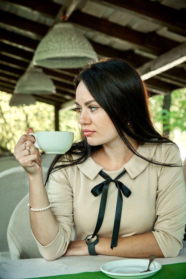 Den unga stilfulla flickan dricker kaffe arkivbild