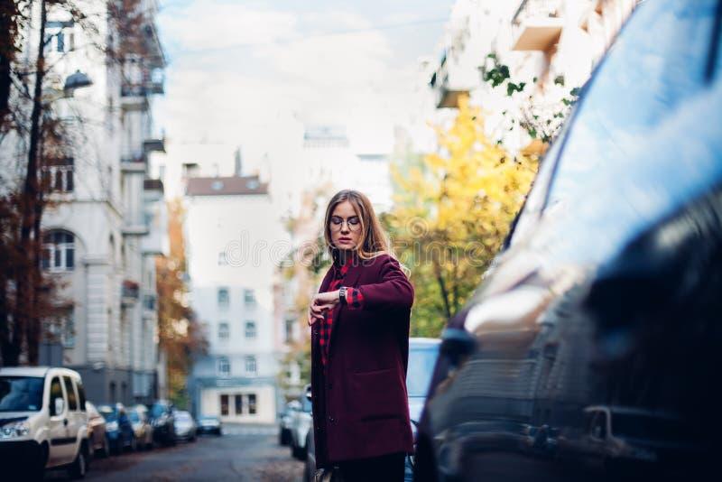 Den unga stilfulla flickan står vid vägen, ser hennes klocka, väntar på en taxi arkivfoto