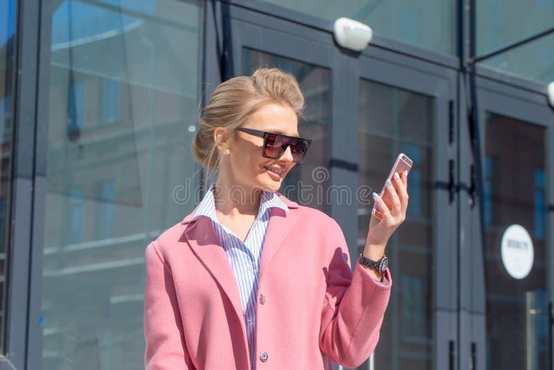 Den unga stilfulla härliga kvinnan i rosa färger täcker att gå i gatan arkivfoto
