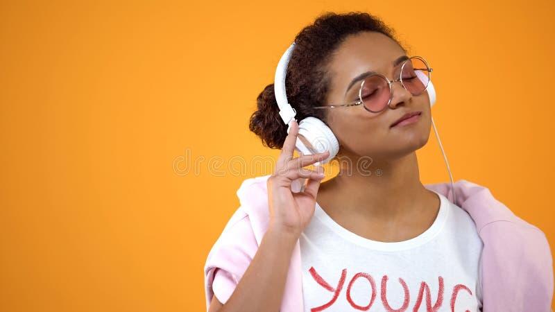 Den unga stilfulla kvinnan som tycker om favorit- musik i h?rlurar, radios?nder applikation royaltyfri bild