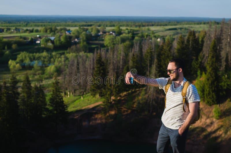 Den unga stilfulla mannen med bärande solglasögon för ett skägg gör selfie på kanjonklippan arkivfoton