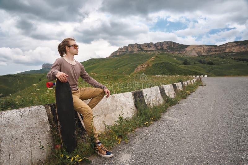 Den unga stilfulla mannen med långt hår i solglasögon sitter på ett käckt med en longboard i hans händer på ett land royaltyfri bild