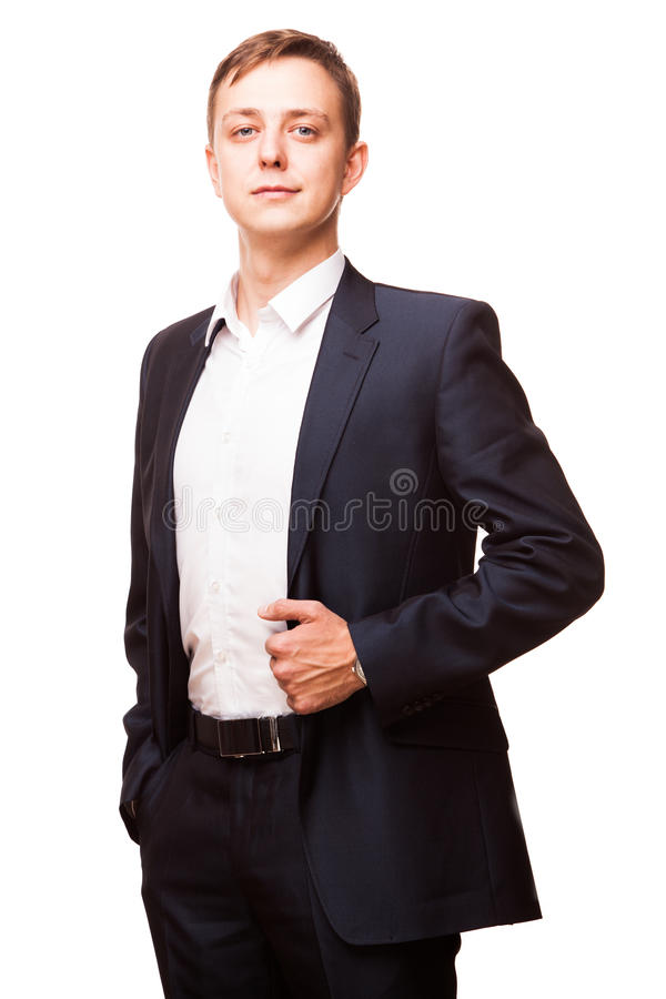 Den unga stiliga affärsmannen i svart dräkt är den stående raksträckan och att sätta hans händer i fack, ståenden som isoleras på arkivfoto