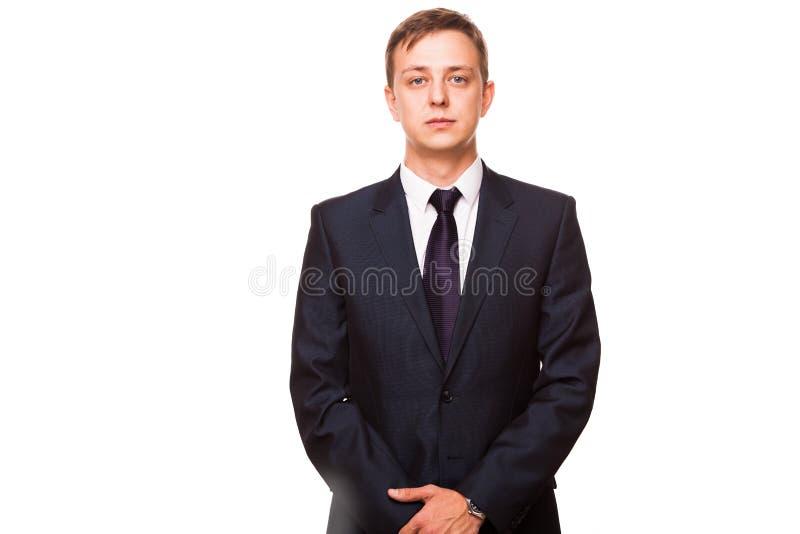 Den unga stiliga affärsmannen i svart dräkt är den stående raksträckan, ståenden som isoleras på vit bakgrund fotografering för bildbyråer